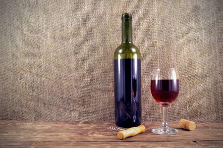 copa de vino: De botella y un vaso de vino tinto sobre una mesa de madera Foto de archivo