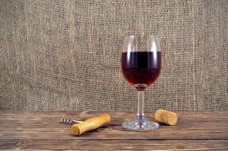 aftertaste: Glass of red wine with a corkscrew and a cork on a wooden table