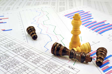 Photos chess pieces with graphs and numbers in the tables Reklamní fotografie