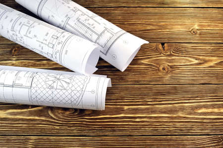 devise: Photo drawings for the project engineering work that lie on background a wooden table Stock Photo