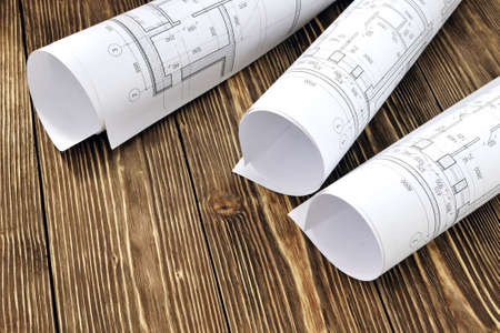 reckon: Photo drawings for the project engineering work that lie on a wooden table Stock Photo