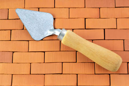 Photo lying trowels on the background of bricks