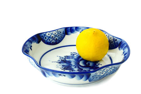 White ceramic vase quadrangular for candies and fruit  It is painted with a blue-blue pattern in Gzhel style  and a lemon  photo