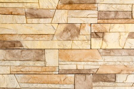 Fragment of a wall of the house covered with a light brown ceramic tile, imitating a natural stone  photo