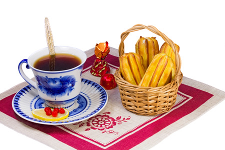 Cup of tea, candies and cakes in the basket are located on a napkin from flax. Presented on a white background. photo