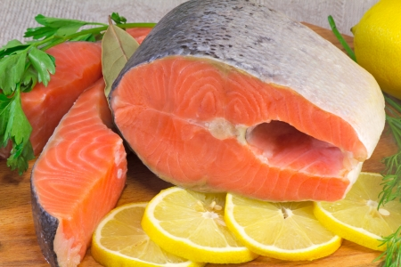 On the table are cut into large pieces of fish salmon, lemon, dill and parsley, spices for cooking fish.
