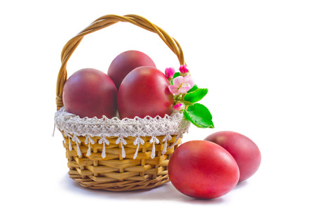 Three Easter eggs, painted in red, are beautifully decorated with wicker basket. Фото со стока
