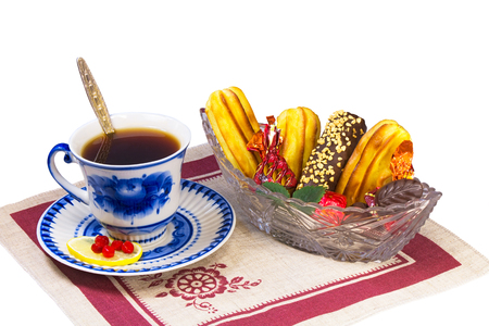 Cup of tea, candies and cakes in the basket are located on a napkin from flax.  photo