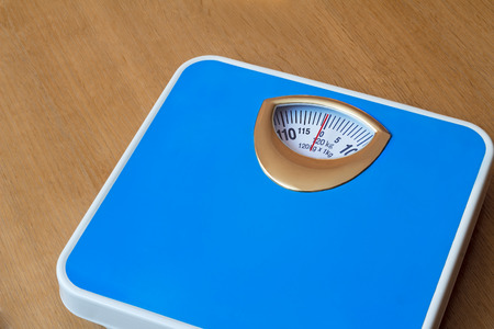 weighing scale: Comfortable scales blue for weighing. Located on the wooden floor.