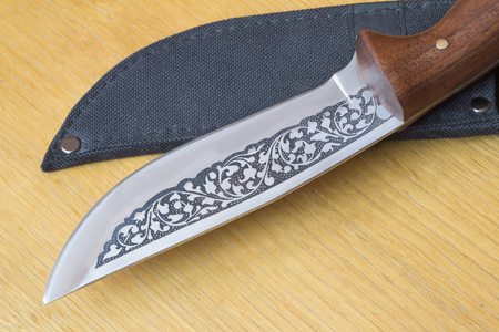Large, beautifully decorated with a hunting knife and black case for a knife. Located on a cutting Board. photo