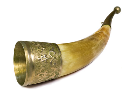 Made from animal horns and decorated with engraving on metal, wine vessel. Presented on a white.