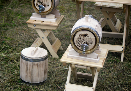 oak barrel: Beautifully decorated with oak barrel with a metal crane, is located on a convenient wooden stand. Stock Photo