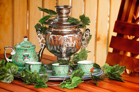 Beautiful large samovar, cups and a kettle are standing on a table in expectation of the guests.  photo