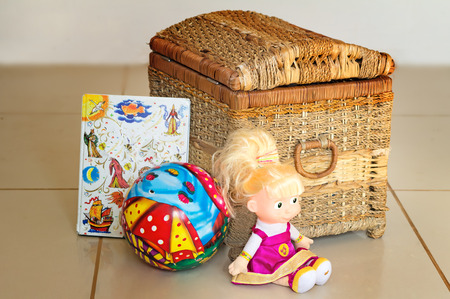 Beautiful childrens toys: doll, ball, book. Are located near the container for storage of toys. photo