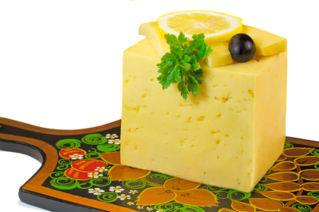 Piece of the yellow porous cheese, the cut slices of cheese, lemon and olives. Are presented on a white background. photo