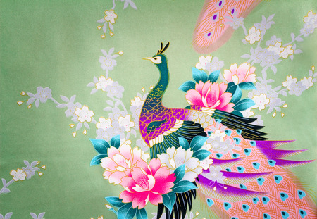 Beautiful silk fabric of light green color with the bright image of a peacock among flowers.g photo
