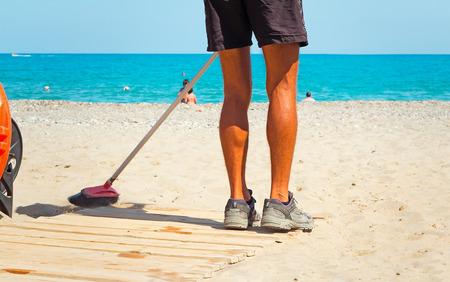 浜辺で、ワーカーは、嵐の後海のビーチの砂の上のゴミをクリーンアップします。 写真素材