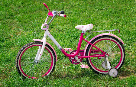 The beautiful bicycle bright pink color for the girl. Is on a lawn with a green grass.  photo