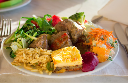 On a cloth of a table the dish with stewed meat, an omelet, vegetables is located. photo