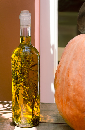 the next life: Still life on a wooden surface of the table is a bottle with olive oil and spices inside the bottle. It is next to the pumpkin. Stock Photo