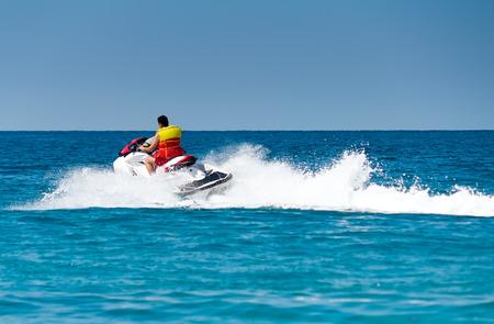 若い男はすぐに海の水のスクーターで行く