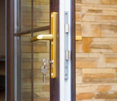 Het fragment ingang glazen deur met slot met handvat en sleutel. Stockfoto - 35045368