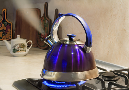 Blue kettle with a signal of boiling water and steam jet from the spout is on the burning gas stove photo
