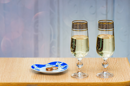 On the table near the window are two beautiful glass filled with champagne. photo