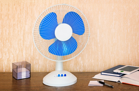 writing materials: On the table is a handy fan with switching speeds , books, writing materials.