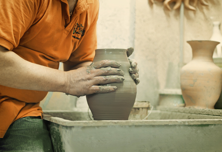 manually: On a rotating pottery wheel wizard manually manufactures ceramic vase.