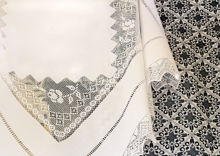 bedspread: A beautiful white tablecloth, decorated with handmade lace, near bedspread is embroidered with a beautiful pattern of dark blue silk threads.