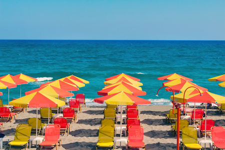 loungers: Umbrellas for sun protection and sun loungers on the deserted beach because of the storm .On waves of the sea. Stock Photo