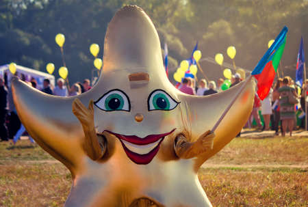 funny costume: Depicts a man in a funny costume in the form of a star with a flag in his hand at the festival. Stock Photo
