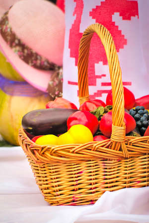 health fair: On a white towel there is a beautiful basket with tomatoes, eggplants, pepper, grapes for sale at fair.