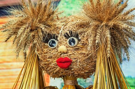 papiermache: Funny doll made of straw and ears of wheat with eyes , eyelashes, mouth of papier-mache.