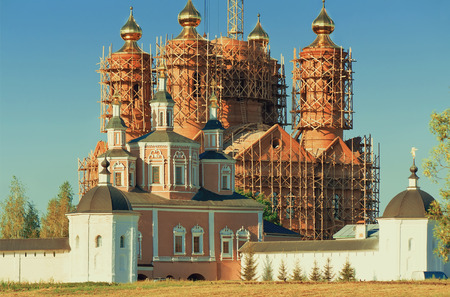erect: Behind a monastery wall visible to erect a temple with gold domes in scaffolding. Stock Photo