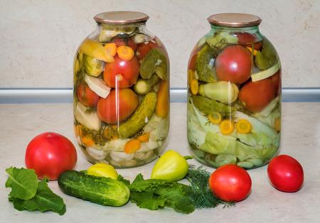 carnes y verduras: Inicio de conservas: grandes cilindros de vidrio con una variedad de verduras: repollo, tomates, pepinos, pimientos. Sellado con tapas de metal. Situado junto a las verduras frescas.