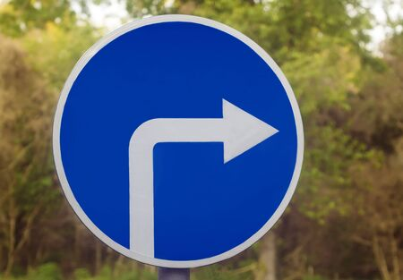 blue arrow: Road sign in the form of a blue circle with a white arrow indicating the allowed twist on the motorway. Stock Photo