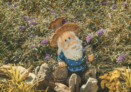 garden staff: n the garden among the flowers on the pedestal with decorative stones stands the figure of a dwarf with a staff and in a funny hat in the shape of a mushroom.