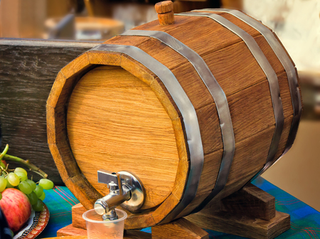 durable: Large durable , made of natural oak, barrel for wine with a metal crane, is located on a convenient wooden stand.