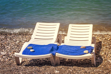 sunbeds: Two sunbeds on the beach near the water, they spread out a beach towel. Stock Photo