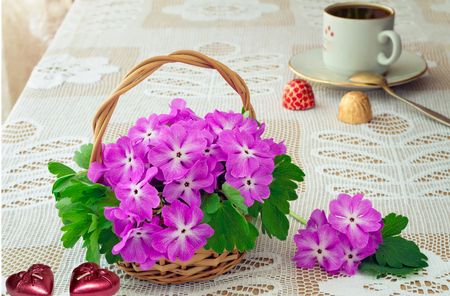 heart burn: On the table in lace fabric features a basket of flowers violets, candles in the shape of a heart, coffee and candy .