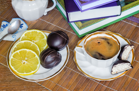 cheerfulness: On the table a Cup of black coffee, milk, candy, lemon. The view from the top. Stock Photo