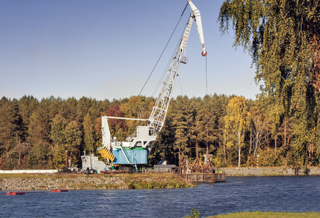 deepening: On the river Bank is a large unit for cleaning the bottom of the river and deepening the river to allow navigation. Along the banks of the river grows a dense forest. Stock Photo