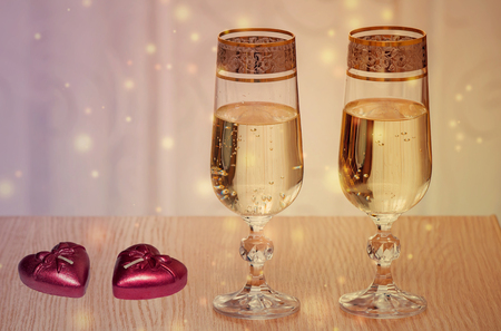 On a table near the window are two beautiful glass filled with champagne. Next two candles in the shape of a heart.