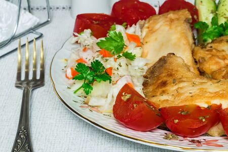 high calorie: On the table is a plate with pieces of delicious fried fish and various basimi.