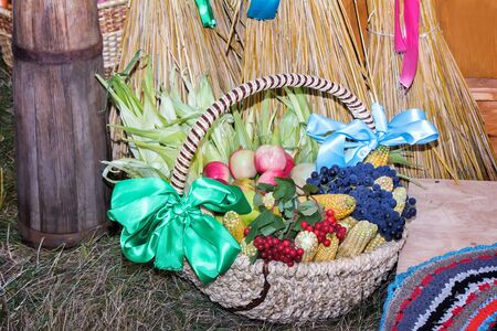 health fair: At the fair selling fruits and vegetables in a basket, decorated with beautiful ribbons. There are sheaves of ears of corn, and objects of rural life. Stock Photo