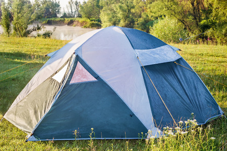 practical: Practical single camping tent of blue-white color on the green meadow by the river.