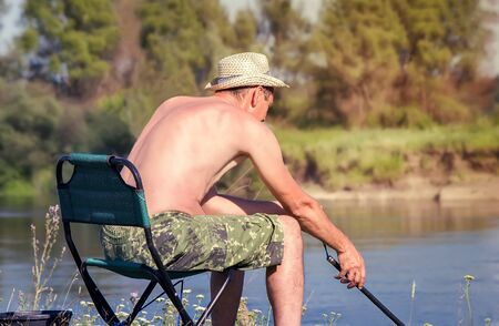 sits on a chair: On the banks of the river on a folding chair sits a fisherman with fishing rod and catch fish. Stock Photo