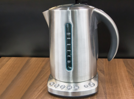 modes: On the surface of the table there is an electric kettle with different temperature modes for heating water.